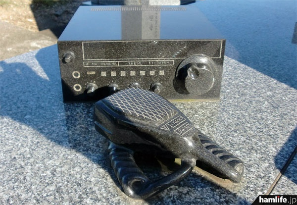 ベース部に置かれた石材彫刻の無線機はハンドマイク付き。「この無線機を使って、いつでもご家族の近況をお父様に伝えられるように」という配慮だという