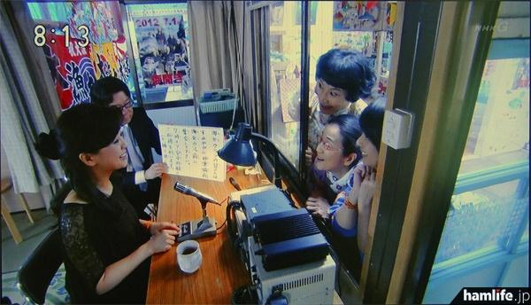 漁協(海女クラブ)の事務所に設置された無線機を前に、スタンドマイクでアナウンスする薬師丸ひろ子。一見するとアマチュア無線の運用シーンのように見える(NHK「あまちゃん」の映像より)