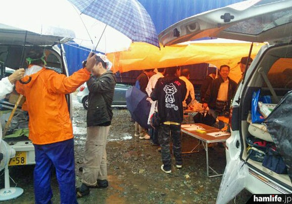 テントや仮設の雨よけシートの下で掘り出し物を探す参加者たち