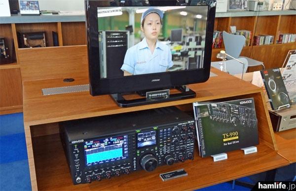 最高級機種・TS-990は専用コーナーに設置され、操作も体験できる。上部のモニターでは山形工場生産ラインのビデオが流されている