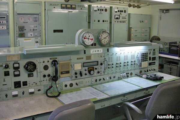 無線通信卓。中央にコールサイン「JHMI」のプレート。その上には沈黙時間入りのアナログ時計が並ぶ=2013年10月9日撮影