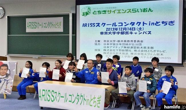 「ARISSスクールコンタクト in とちぎ」に参加した15名の小中学生による記念写真。つなぎを着ている子供たちは「宇宙少年団」に所属している