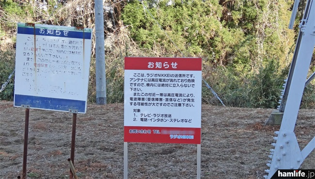敷地内に立つ「お知らせ」の看板(左は「ラジオたんぱ」時代のもの)。周囲はほとんどが山林で、一部に別荘地とキャンプ場がある