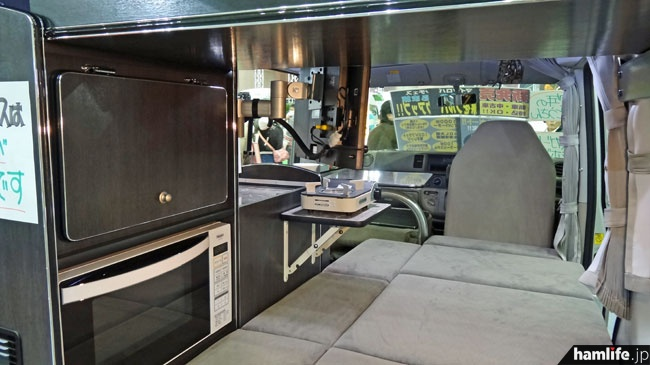 1人用キャンピングカーの内部。1000Wインバーター、19型BS/CS対応テレビ、電子レンジ、冷蔵庫、100Wソーラーシステム、走行中充電も可能なサブバッテリーなどを搭載。お手軽移動運用に最適!?(リンエイプロダクト)
