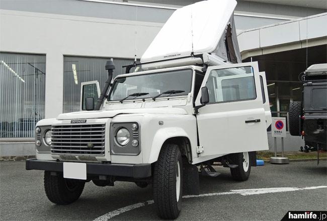 「白」のランドローバー・ディフェンダーの外観。上部にはポップアップ式のカートップテントを装備。エアインテークは渡河を考慮しAピラー上部に延長