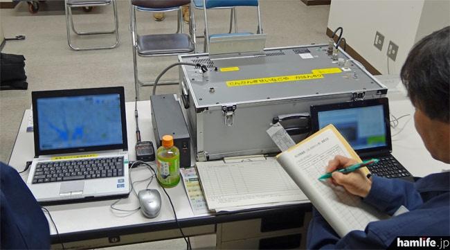 規正用無線局は接続したノートパソコンで操作。「ただちに電波の発射を中止しなさい」など、違反局に警告や運用中止を命ずる音声が送信できる。受信した内容の保存も可能。 左にあるのは電波監視システム「DEURAS(デューラス)」の操作端末。各地に設置された「センサ局」を操作して、不法局の現在位置を極めて高い精度で割り出すことができる