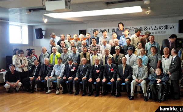 「第42回青森県支部大会・ハムの集い」の記念写真最前列中央にJA7AIW・山之内JARL会長(東北地方本部長を兼務)が着席している