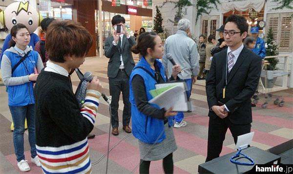 来場者や関係者にインタビューをする、FMいるかの番組スタッフ