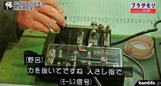 野呂氏の説明より早く、縦ぶれ電鍵で「CQ CQ JA6…」と打ち始めるタモリ(NHK「ブラタモリ」の映像より)