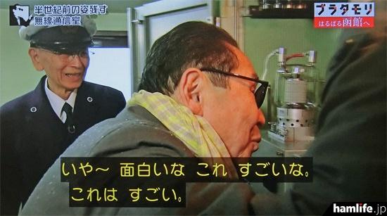 目を凝らして送信機の内部を見るタモリ(NHK「ブラタモリ」の映像より)