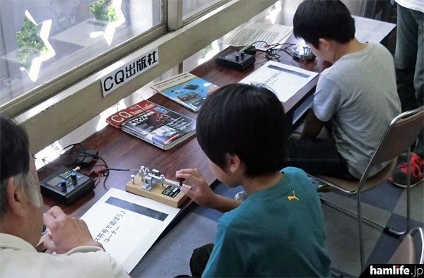 CQ出版社はオリジナル電鍵とモールストレーナーを設置し、モールス符号の試打ができるコーナーを設けた