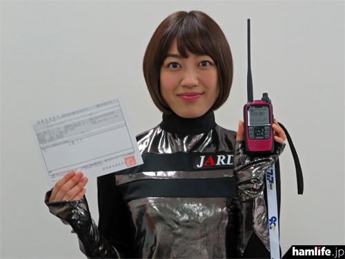 自身の無線局免許状とD-STARハンディ機を手にした松田百香