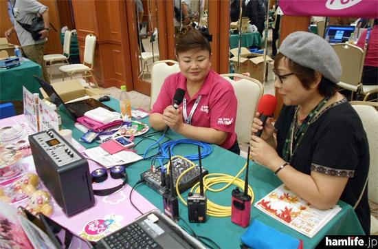 会場ではFMぱるるんの「CQ ham for girls」の番組収録も行われた。番組MCの水田かおり(左)が、JP7ELN 中里さんにインタビュー中の模様