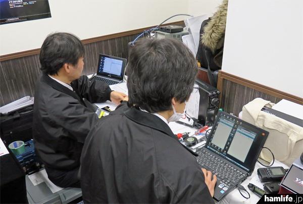 会場奥では八重洲無線の技術スタッフが、次々に持ち込まれるC4FM対応機のファームウェアの更新サービスに追われていた