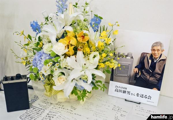 「JA1AMH 高田継男さんを送る会」会場に飾られた写真パネルと盛花