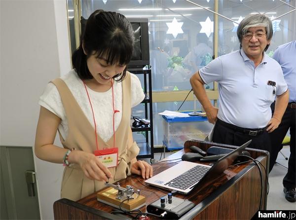 子供たちにモールス符号を出題する女優の松田百香(JI1NYO)。写真右は特別ゲストのARISS運用委員、安田 聖氏(7M3TJZ)