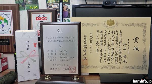 野崎氏が受賞した「世界10,000局よみうりアワード」の賞状と楯、記念品
